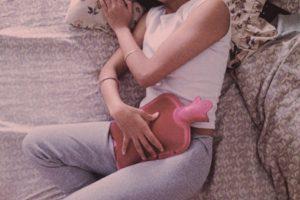 Mujer recostada en la cama con bolsa de agua caliente para calmar los cólicos. Esta imagen busca el empoderamiento femenino y el cese de los estigmas del periodo.